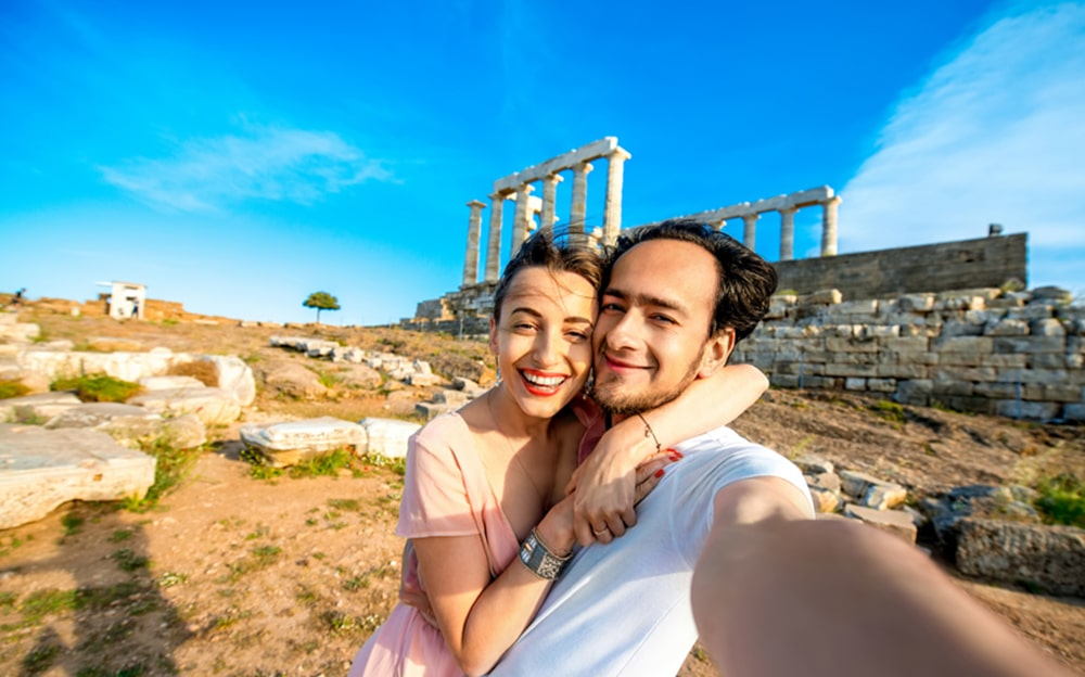 Couple taking selfie next to Cape Sounion.