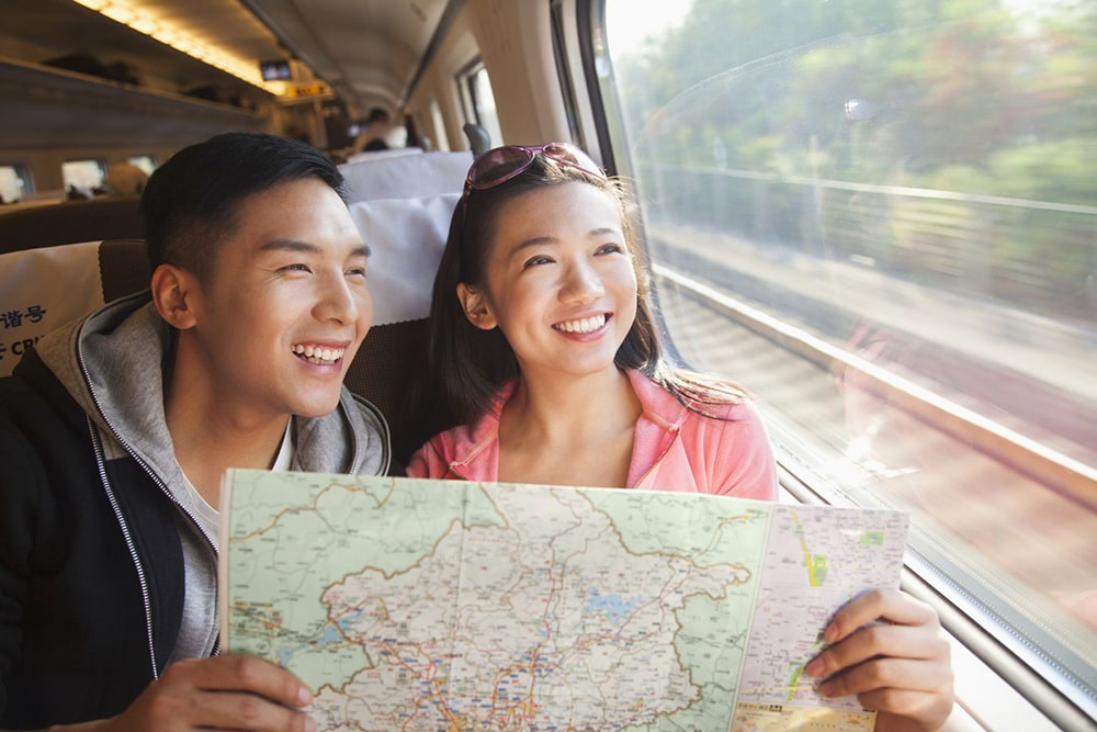A couple in the train smiling and holding a map.