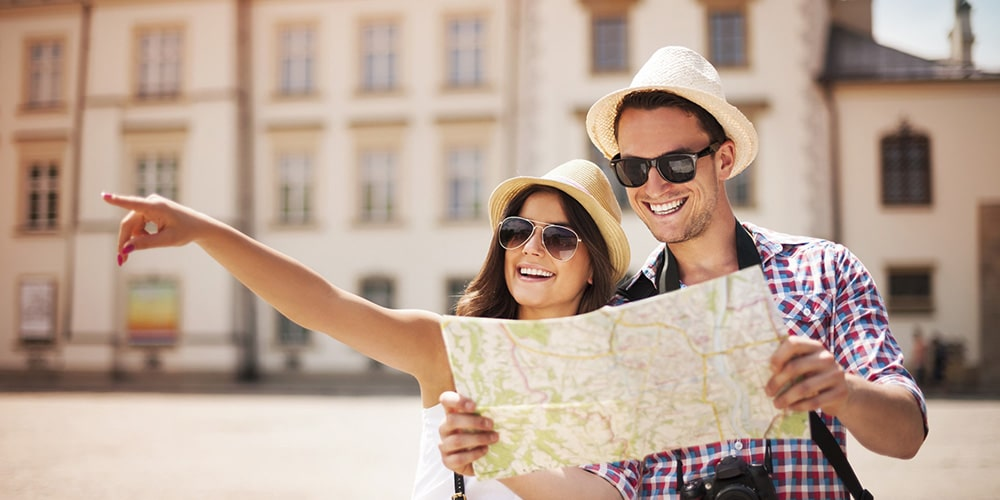 A woman pointing forward and a man holding a map.