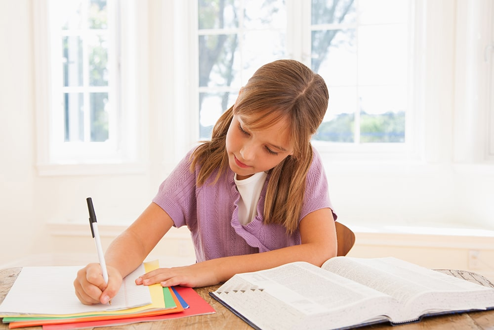 Girl writing in her notebook.