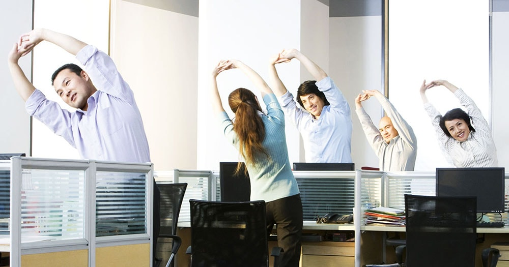 Office workers doing exercises at their working places.