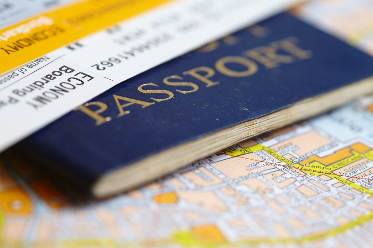 The passport with the tickets laying on the map