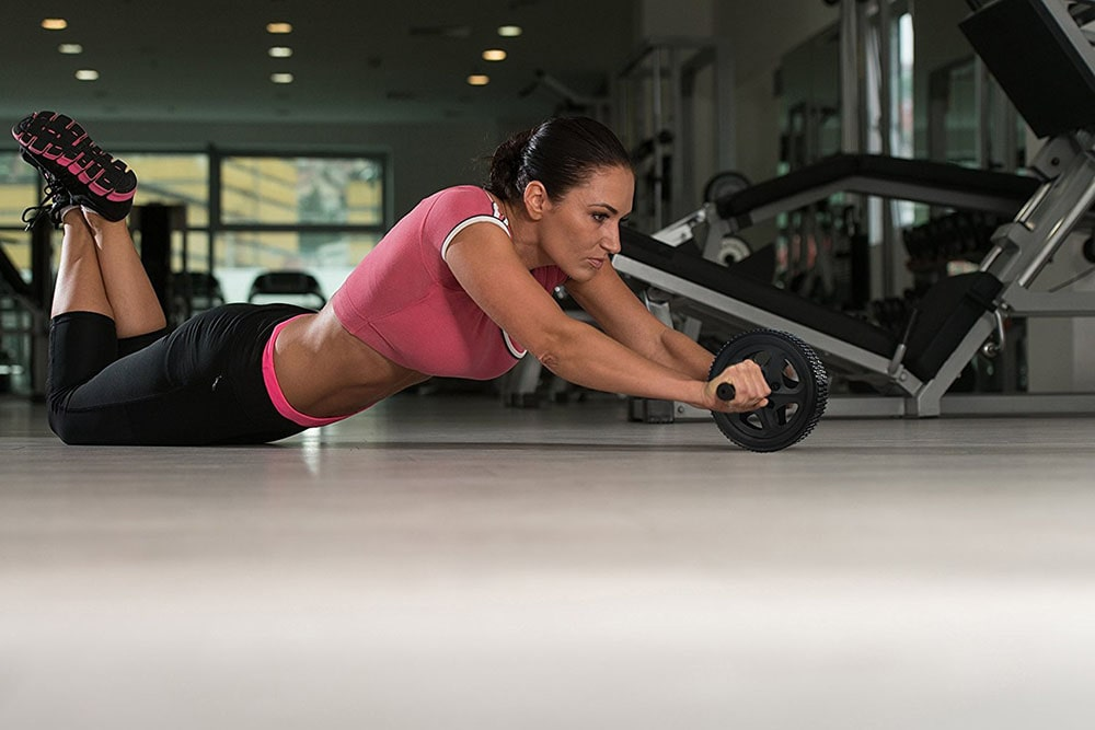Woman working out with roller wheel.