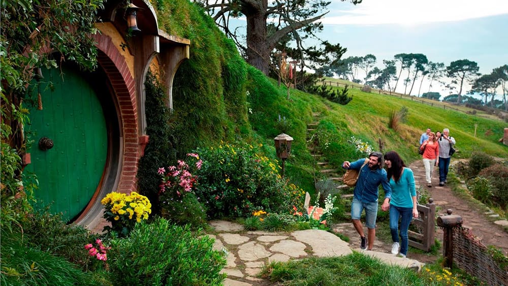 People are walking to the Hobbit's hole.
