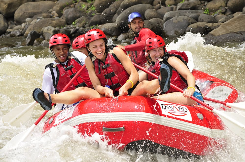 People whitewater rafting and smiling.