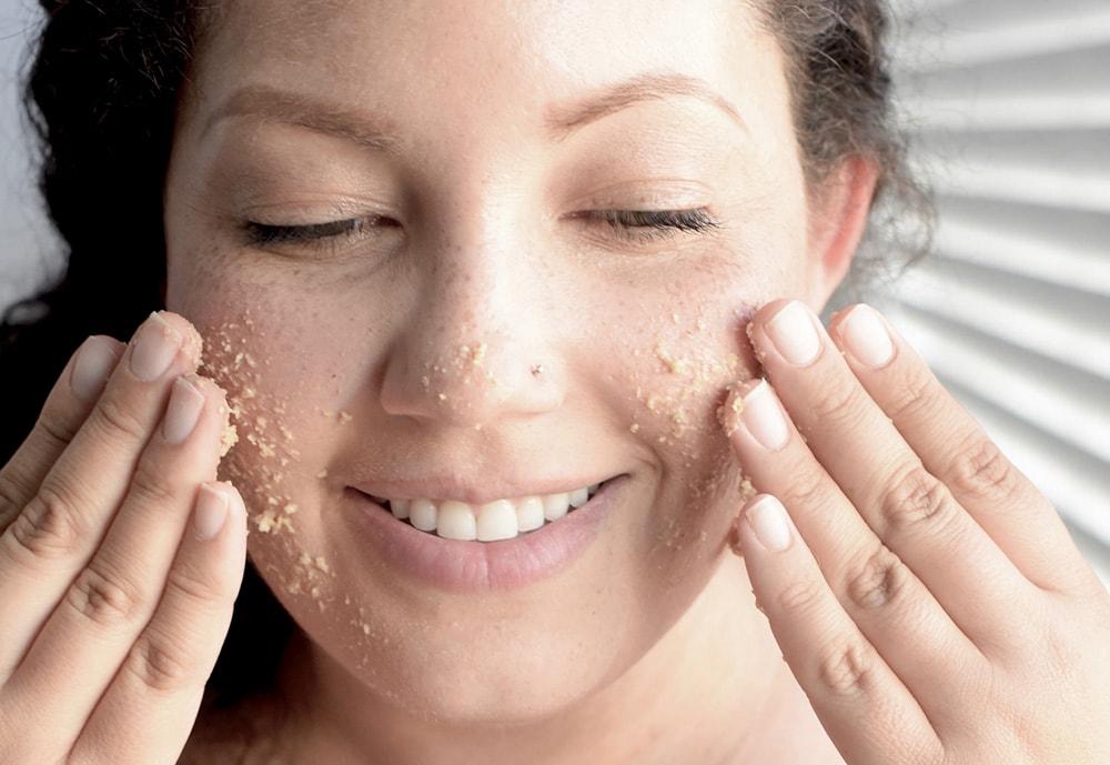 Woman applying face scrub.