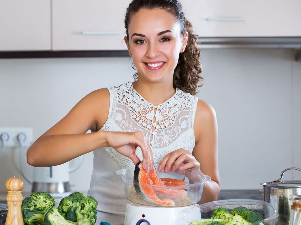 Woman cooking salmon in a steam cooker.