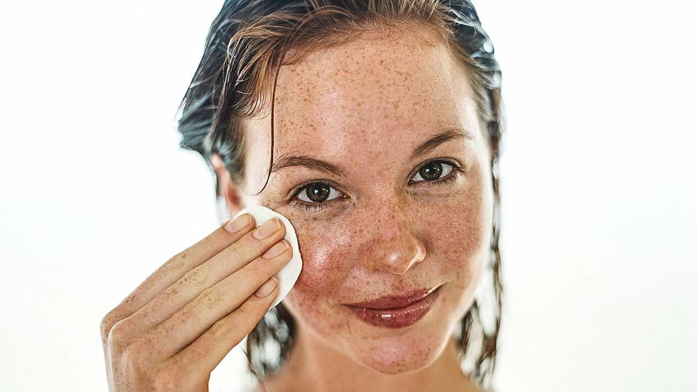 Woman using face cotton pad.