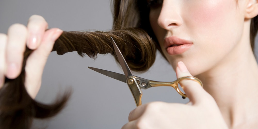 Woman holding scissors and her hair lock.