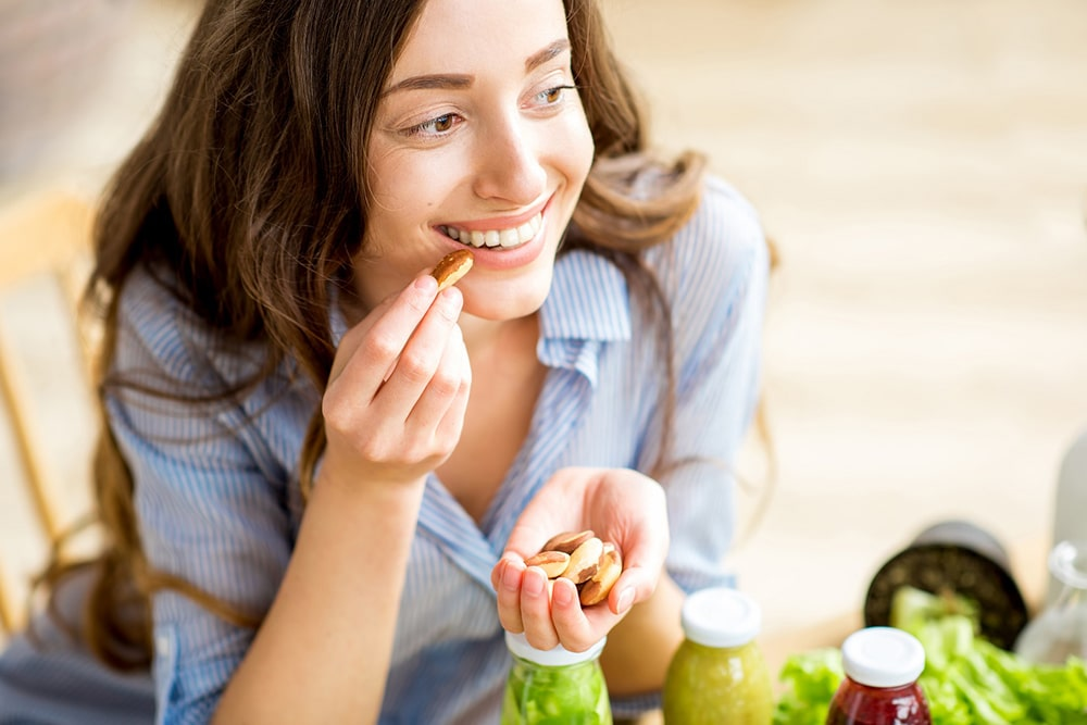 Woman eating nuts from her hand.