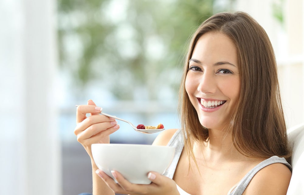 Woman eating oatmeal with fruits.