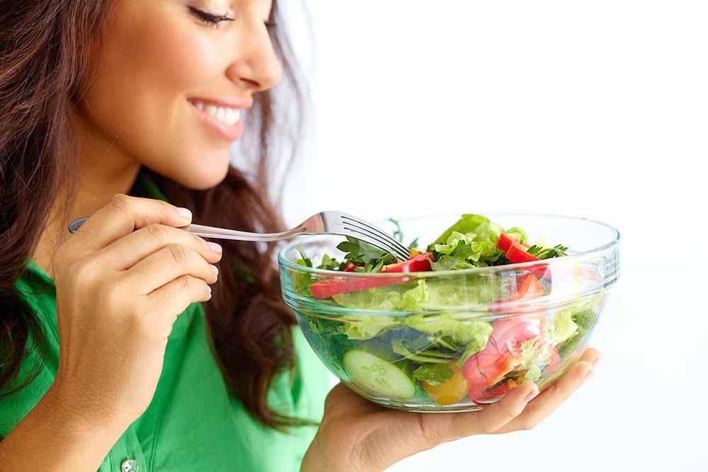 Woman eating a bowl of salad.