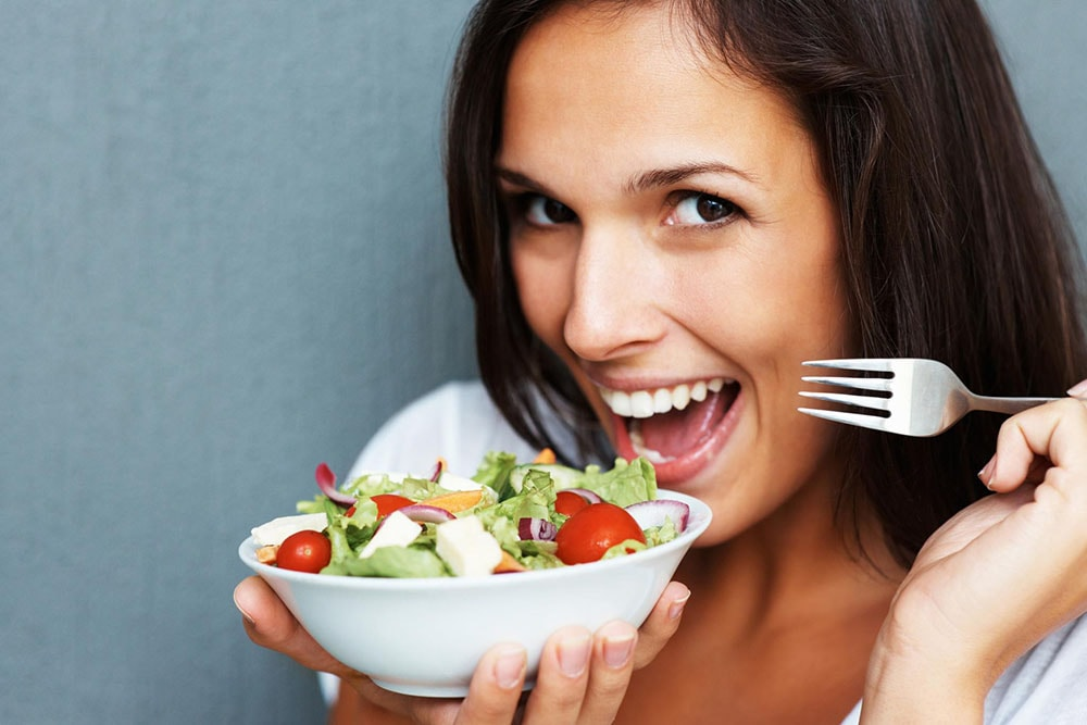 Woman holding a bowl of salad and a fork.