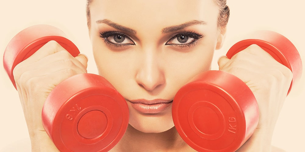 Woman holding dumbbells next to her face.