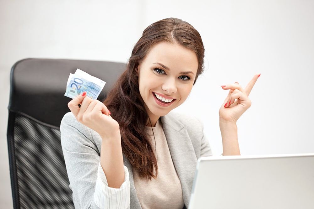 Woman sitting in front of the laptop and holding money.