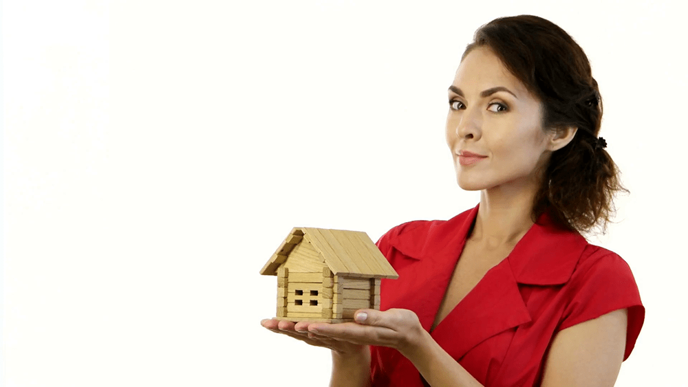 Woman holding a toy house.