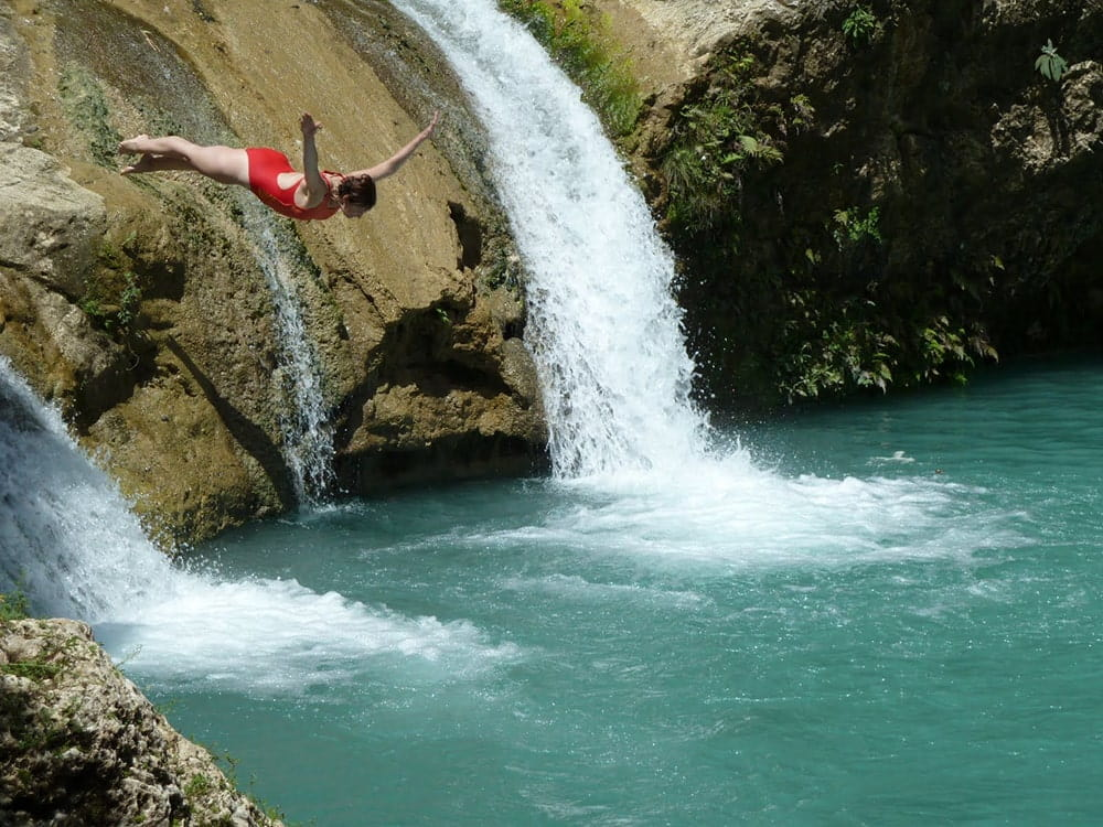 Woman jumping into the water next to the waterfall.