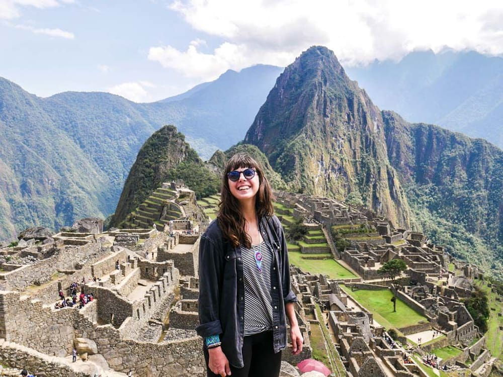 Smiling woman standing in front of Machu Picchu.