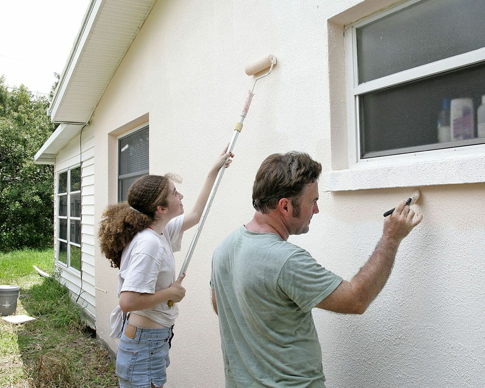 A man and a woman painting a house.