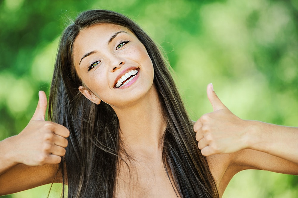 Woman with long hair holding thumbs up.
