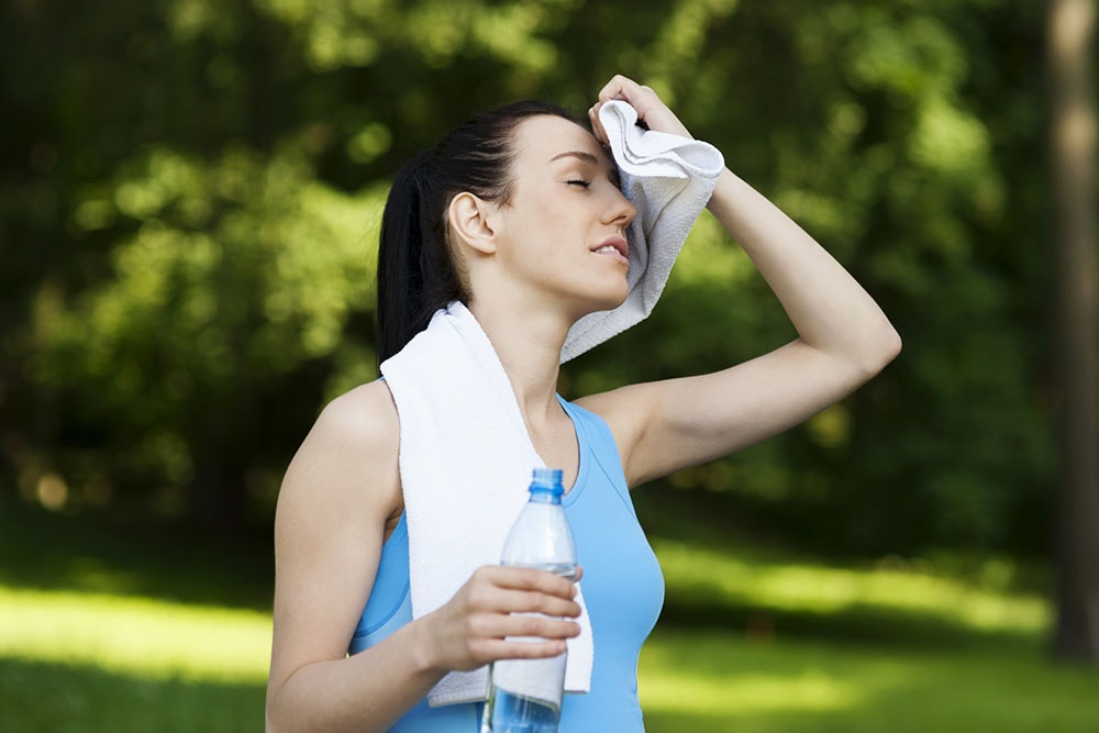 Woman wiping sweat with towel.
