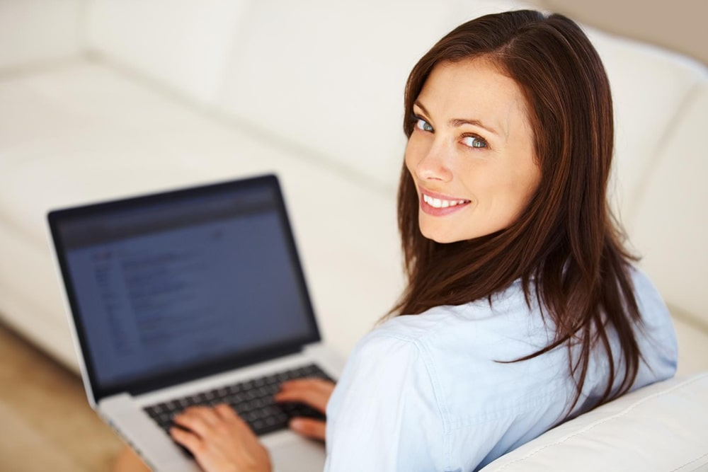 Smiling woman with a laptop on her knees.