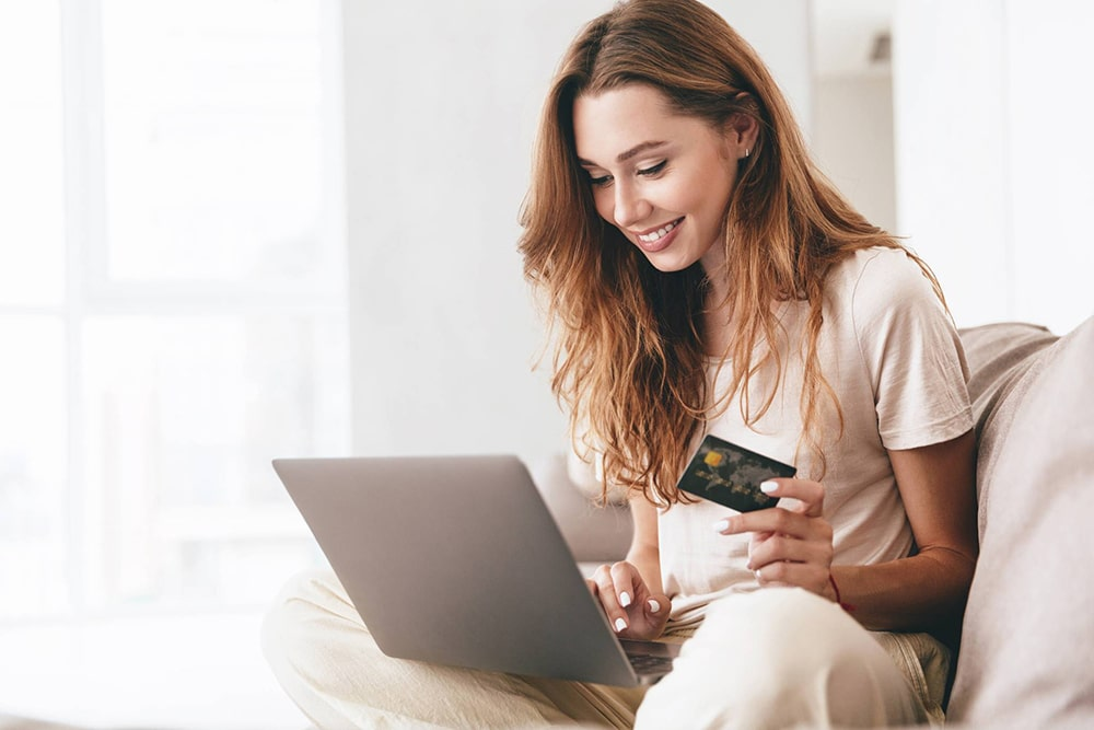 Woman working on a laptop and holding a credit card.