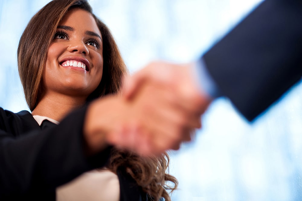 Smiling woman shaking hands with someone.