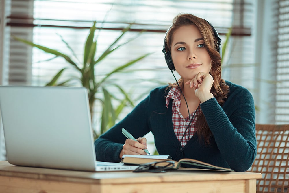 Woman wearing headphones sitting at her desk.