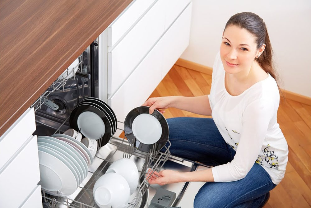 Woman using dishwasher.