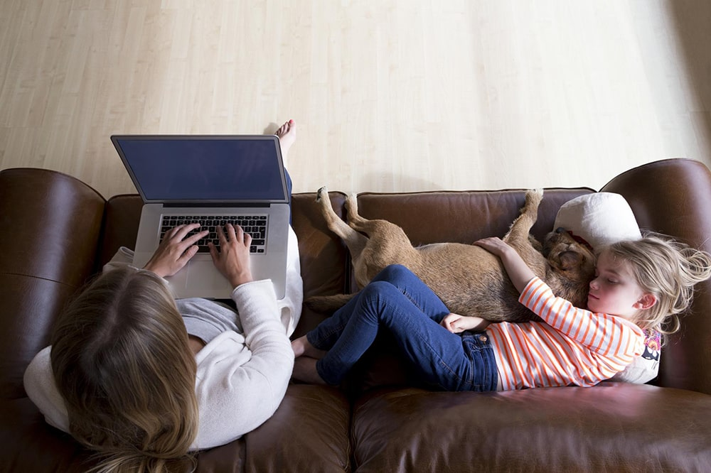 Woman sitting on a sofa with a girl and a dog.