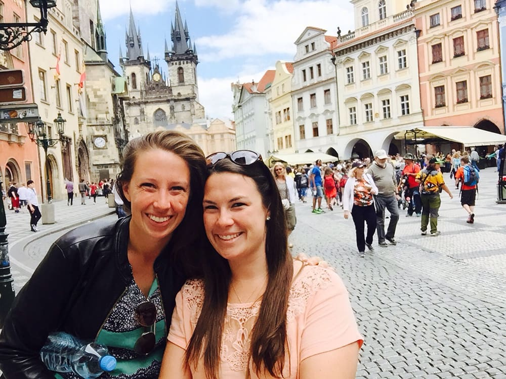 Two smiling women standing on the Old City Square.