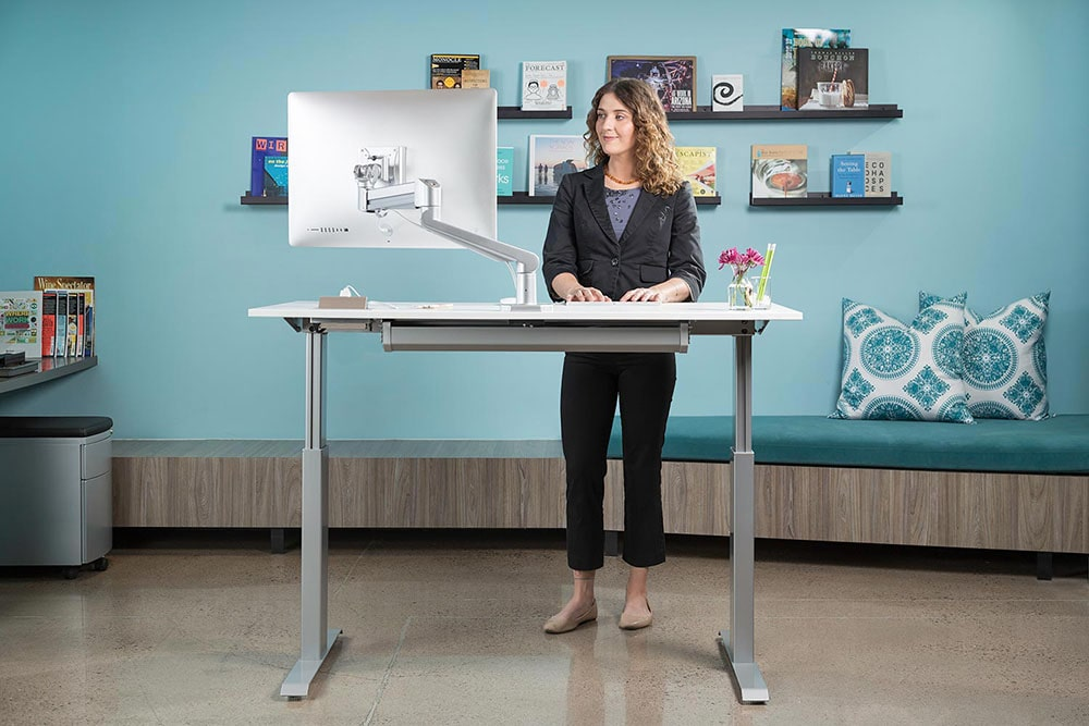 Woman working at a standing desk.
